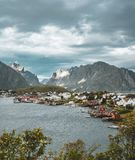 Landscape of fishing village Reine with the Reine Fjord during sunset with nice lights on mountain, blue sky and clouds. Lofoten, Norway. Photo taken in Norway royalty free stock photo