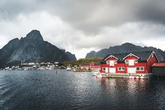 Landscape of fishing village Reine with the Reine Fjord during sunset with nice lights on mountain, blue sky and clouds. Lofoten, Norway. Photo taken in Norway stock image