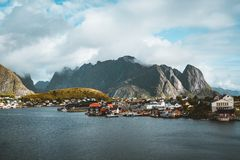 Landscape of fishing village Reine with the Reine Fjord during sunset with nice lights on mountain, blue sky and clouds royalty free stock photography