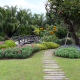 Landscape of floral gardening with pathway and bridge Royalty Free Stock Images