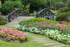 Landscape of floral gardening with pathway and bridge. In garden Stock Photography