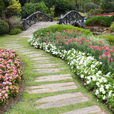 Landscape of floral gardening with pathway and bridge Royalty Free Stock Photography