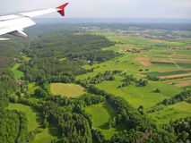 Landscape with forest, fields and airplane wing - aerial view during landing Stock Photos