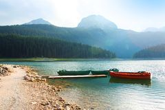 Landscape with forest and lake. Beautiful mountain landscape with colorful lake and boats Stock Photography