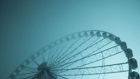 Blue-tinted image of a large ferris wheel on a cold morning. A landscape formatted image of a blueish tinted and large ferris wheel Stock Images