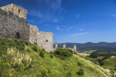 Landscape with fragment of medieval castle. Landscape with the bright green vegetation, blue sky and a fragment of the ramparts of a medieval castle royalty free stock photography