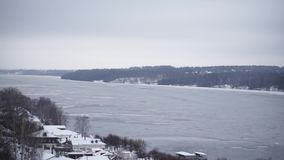 Landscape with a frozen lake and mountains with pine trees and Church. The Church stands on a hill above a frozen lake stock video footage