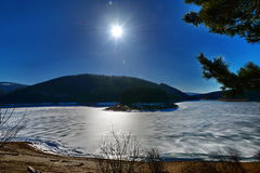 Landscape with frozen lake and sun. Stock Image