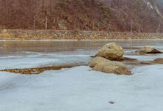 Landscape of frozen river with rocky shoreline. And large boulders in foreground on a cold overcast winter day Stock Image