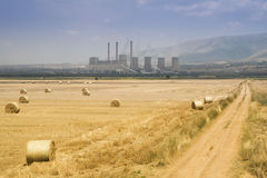 Landscape with  fuel-burning power plant and round rickы, Greece. Round bales of straw in the meadow near the fuel-burning power plant, Greece Royalty Free Stock Images
