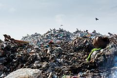 Landscape of the garbage dump full of smoke, litter, plastic bottles,rubbish and trash at tropical island. Landscape of the garbage dump full of smoke,litter Stock Photos