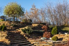 Landscape garden design on a hill, lined with stone and planted stock photo