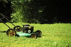 Landscape gardening and landscaping concept. Lawn mower on green grass on sunny day in natural background. Landscape gardening and landscaping concept. Lawn Stock Photo