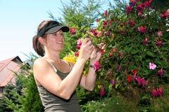 Landscape Girl. A woman landscape gardener smiles as she prunes a hanging basket full of flowers Royalty Free Stock Image