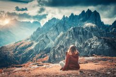 Landscape with girl, cloudy sky, orange grass, high rocks royalty free stock image