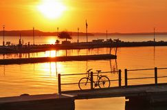 Landscape with golden sunset. Over the lake Mendota. Setting sun reflects in a water with piers and silhouette of bicycle on a foreground. Scenic view from Stock Image
