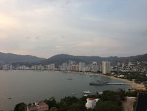 Landscape of the Golden zone of Acapulco Bay, during sunset. Tourist destination in the State of Guerrero, in the Ocean Pacific of Mexico, for trips and restful Royalty Free Stock Photo