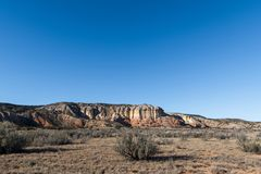 Landscape of grass, sagebrush, and colorful cliffs under a vast blue sky in a high desert landscape in New Mexico stock images