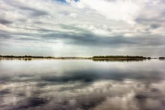 Landscape. Gray-white clouds against the blue sky reflected in the river Royalty Free Stock Photo
