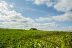 Landscape of a green field with a house in the background stock image