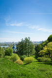 Landscape with green grass, blue sky, church, city Royalty Free Stock Image