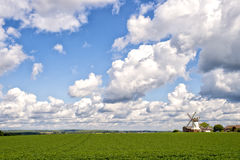 Landscape with green grass, cloudy sky and windmill Royalty Free Stock Images