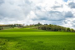 Landscape with green grass, trees and monastery up the hill under cloudy sky stock photography