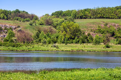Landscape of a green grassy hills, trees, river and sky Stock Image