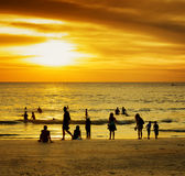 Group of people on sunset beach Stock Photography