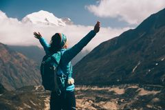 Landscape with happy girl, mountains, blue sky with clouds. Standing young woman with backpack and raised up arms on the hill and looking on mountains. Landscape Royalty Free Stock Images