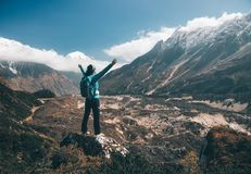 Landscape with happy girl, mountains, blue sky with clouds. Standing young woman with backpack and raised up arms on the hill and looking on mountains. Landscape Royalty Free Stock Image