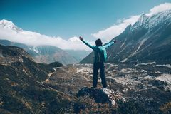 Landscape with happy girl, mountains, blue sky with clouds. Standing young woman with backpack and raised up arms on the hill and looking on mountains. Landscape Stock Photo