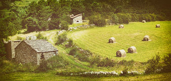 Landscape with harvested bales of straw in field and stone house Royalty Free Stock Photo