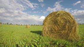 Landscape with hay bales on summer field and rainbow. Timelapse 4K stock video footage