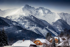 Landscape of high Austrian Alps with traditional houses covered Royalty Free Stock Photo