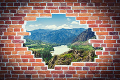 Landscape of high mountains. And a mountain river with green forests in summer on a background of bricky old wall stock photos