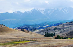 Landscape with a highland valley and snowy mountains Royalty Free Stock Photo