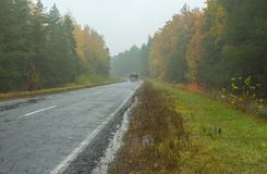 Landscape with highway, rainy weather and lonely motor transport Royalty Free Stock Image