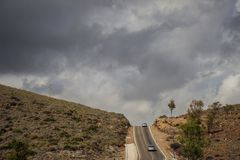 Landscape hills. Cars spain trees street  clouds contrast Royalty Free Stock Photo