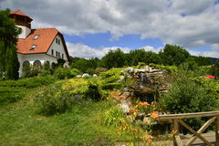 Landscape with house, garden and artificial waterf Royalty Free Stock Images