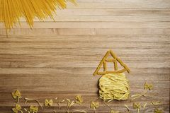 Landscape with a house made of pasta. Landscape with house, flowers and sun from spaghetti and pasta on a wooden background royalty free stock photos