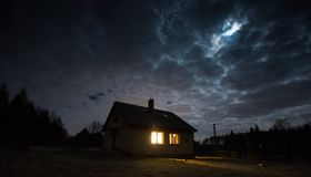 Landscape with house at night under cloudy sky Stock Photos