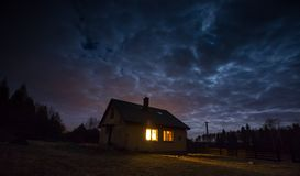 Landscape with house at night under cloudy sky Stock Photography