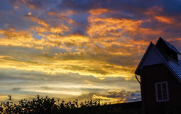 Landscape of house at sunset. Sunset with bright clouds over the house Royalty Free Stock Image