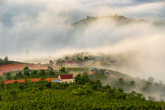 Landscape of houses on the mountain on foggy day Royalty Free Stock Images