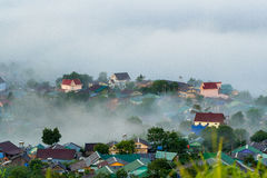 Landscape of houses on the mountain on foggy day Stock Image