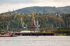 Landscape of a huge industrial construction. Several working cranes on the river, barges with cargo and on a background of a industrial city with small houses stock photo