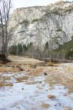 Landscape of Ice Forming on Banks of River with Forest and Mount royalty free stock image