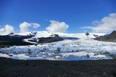 Landscape of icebergs, water and black rock at Jökulsarlon glacier lagoon, Iceland royalty free stock photography
