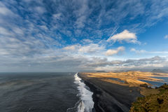 Landscape in Iceland with Blue Cloudy Sky, Ocean Waves and Mountains. Royalty Free Stock Photos